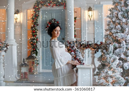 Portrait of brunette girl in anticipation of the baby in a white dress in the interior decoration of the New Year and, standing on the stairs, on the background of the falling white snow