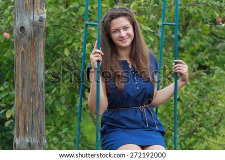 Portrait of brunette girl in navy blue sundress is sitting on handmade swing - stock photo