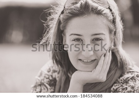 Portrait of brunette girl on sunny spring or summer day in park (Black-and-white photo)