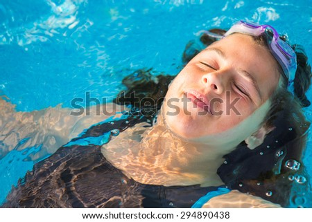 Portrait of brunette girl relaxing at swimming pool - stock photo