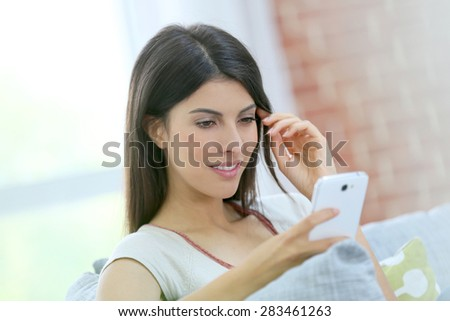 Portrait of brunette girl using smartphone at home