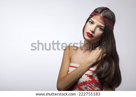 Portrait of brunette girl with the Belarusian flag and ribbon in her hair on a gray background