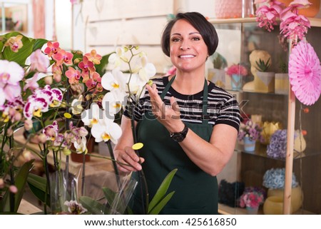 Portrait of brunette happy female florist arranging a phalaenopsis in the gardening department - stock photo