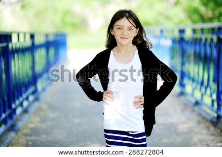 Portrait of brunette kid girl in glasses and fashion outfit outdoor in the park - stock photo