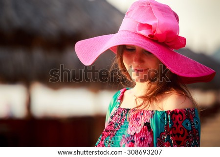 portrait of brunette longhaired girl in big red hat looking down against defocused reed umbrella