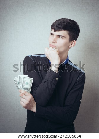 portrait of brunette man upset holding money - stock photo