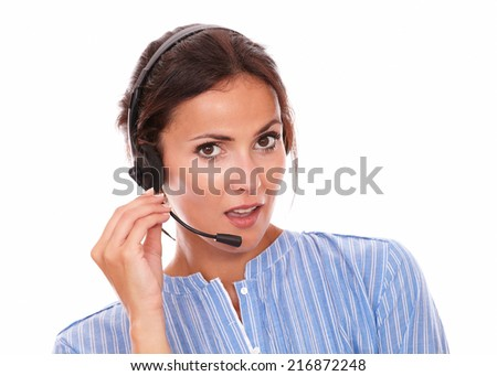 Portrait of brunette operator lady on blue blouse speaking on headphones while smiling at you on isolated studio