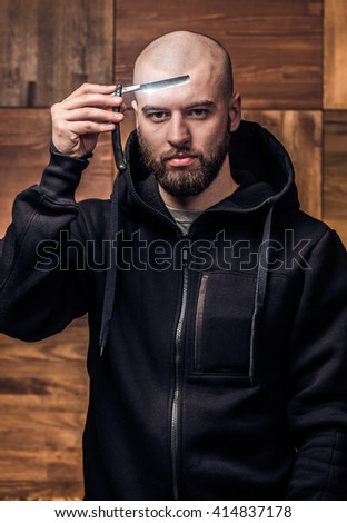 Portrait of brutal bald man with vintage straight razor on a wooden texture in barbershop. Portrait of hipster holding straight edge razor against wooden wall.