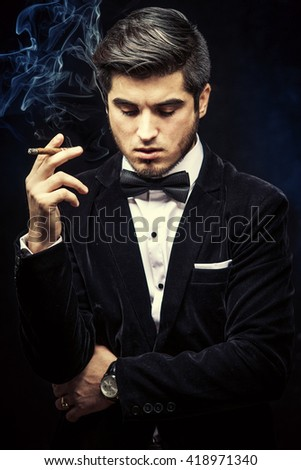 Portrait of brutal handsome man in jacket smoking a cigarette - stock photo