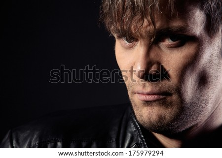Portrait of brutal man in a leather jacket