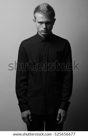 Portrait of brutal young man with short blond hair and freckles on face wearing black shirt, jeans and posing over gray background. Hipster style. Monochrome studio shot