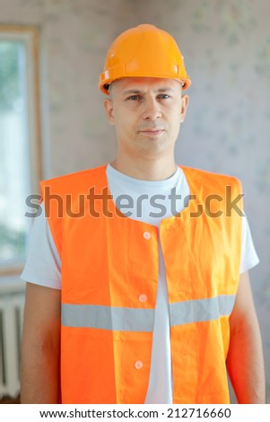 Portrait of builder at new house - stock photo