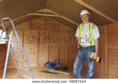 Portrait of builder standing by ladder with hard hat and high visibility jacket - stock photo
