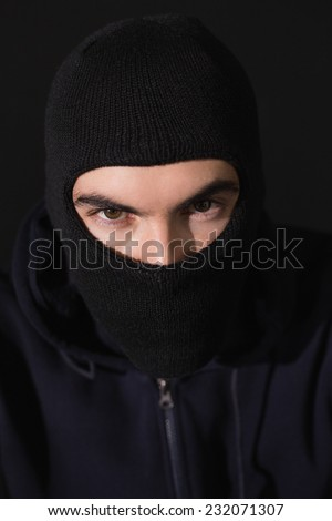 Portrait of burglar wearing a balaclava on black background