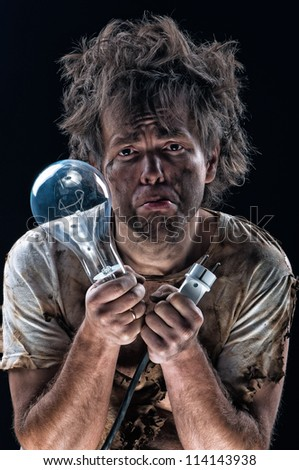 Portrait of burnt man with light bulb and electric plug over black background - stock photo