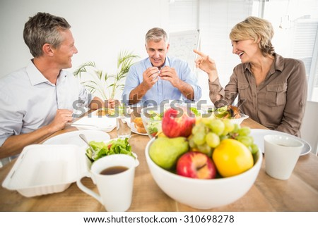Portrait of business colleagues having lunch together at office - stock photo