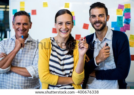 Portrait of business colleagues smiling at camera in the office - stock photo