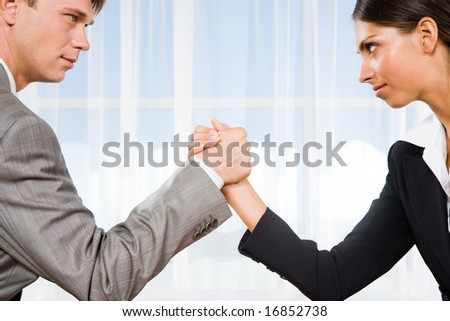 Portrait of business competitors doing arm wrestling and looking into each otherâ??s eyes