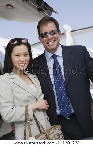 Portrait of business couple standing with airplane in the background at airfield - stock photo