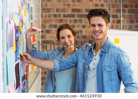 Portrait of business executives putting sticky notes on whiteboard in office