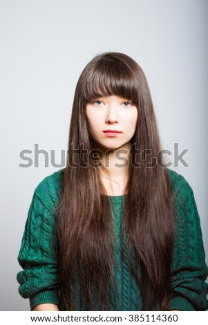 Portrait of business girl with a serious face, isolated on a gray background - stock photo