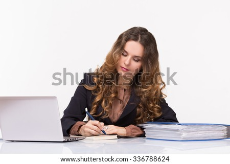 Portrait of business lady writing something in her notebook. Businesswoman working in the office with her laptop computer. - stock photo