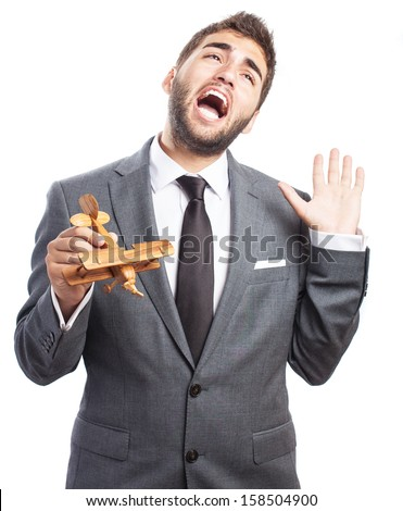 portrait of business man holding a wooden airplane falling down on white
