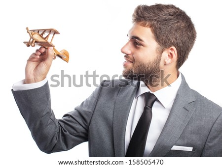 portrait of business man holding a wooden airplane isolated on white