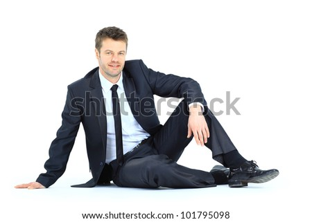 Portrait of business man sitting on the floor isolated over white background - stock photo