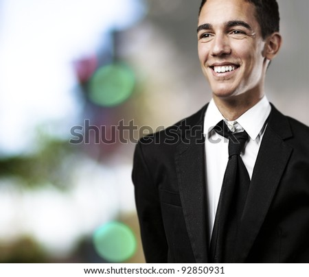 portrait of business man smiling against a lights background - stock photo