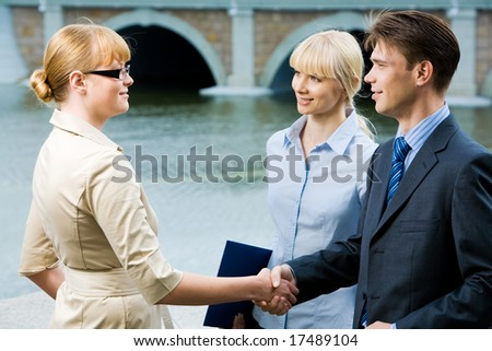 Portrait of business partners handshaking at meeting and looking at each other