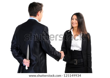 Portrait of business partners handshaking while male holding knife behind her back - stock photo