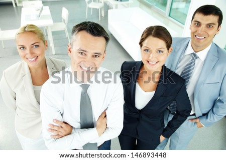 Portrait of business partners looking at camera with their leader in front