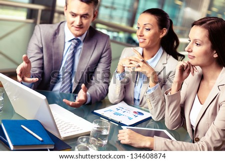 Portrait of business partners looking at laptop display at meeting, focus on pensive female - stock photo