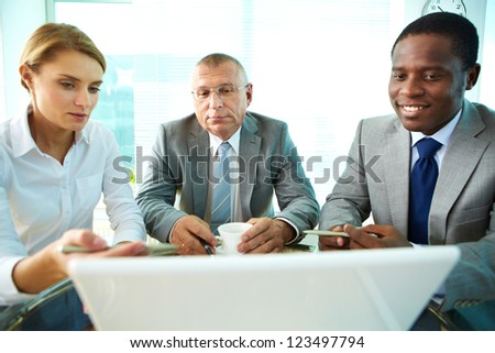 Portrait of business partners looking at laptop screen while female explaining something to her boss and colleague - stock photo
