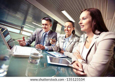 Portrait of business partners pointing and looking at laptop display at meeting - stock photo