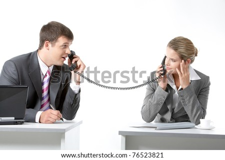 Portrait of business partners speaking on the telephone and looking at each other - stock photo