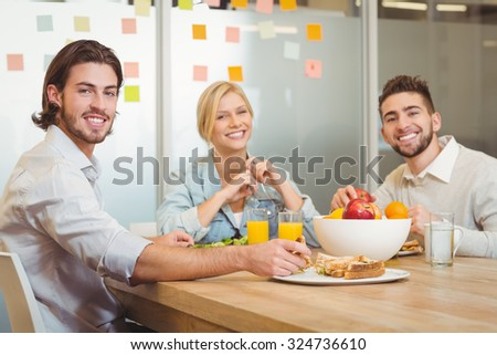 Portrait of business people having lunch in creative office - stock photo