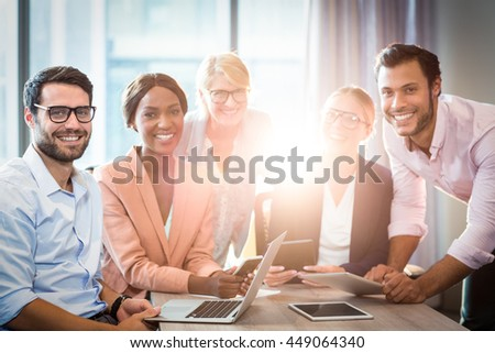 Portrait of business people holding laptop, mobile phone and digital tablet in the office