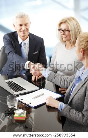 Portrait of business people shaking hands while sitting at business seminar at office.  - stock photo