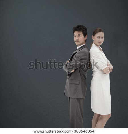 Portrait of business people standing back-to-back against grey background - stock photo