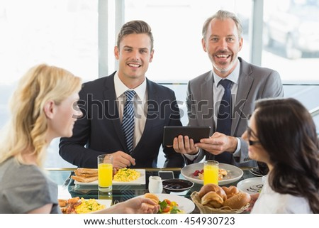 Portrait of business people using digital tablet while having meal in restaurant