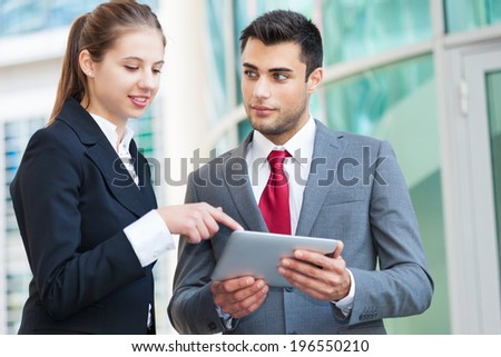 Portrait of business people working on a tablet - stock photo