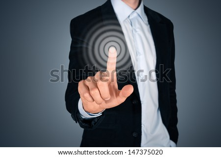 Portrait of business person touching button on invisible screen. Touch screen concept image. Isolated on dark gray background.