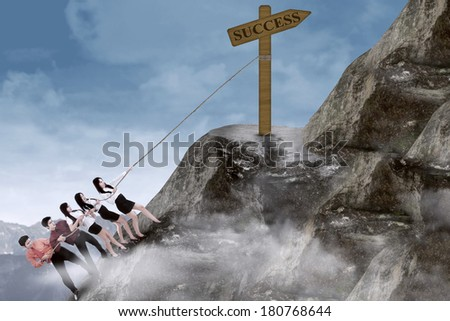 Portrait of business team climbing a success sign using rope on the mountain - stock photo