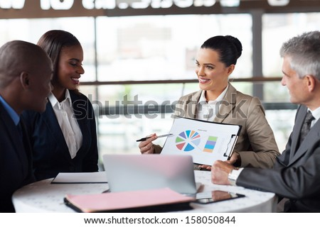 portrait of business team discussing market share in a meeting - stock photo