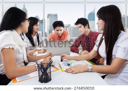 Portrait of business team in a business meeting with their leader, shot in the office - stock photo