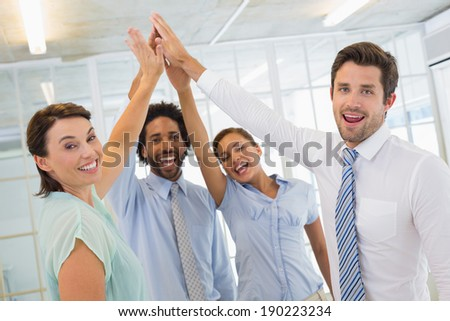 Portrait of business team joining hands together in bright office - stock photo