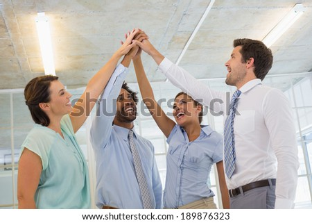 Portrait of business team joining hands together in the office