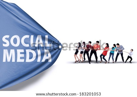 Portrait of business team pulling together a banner of social media